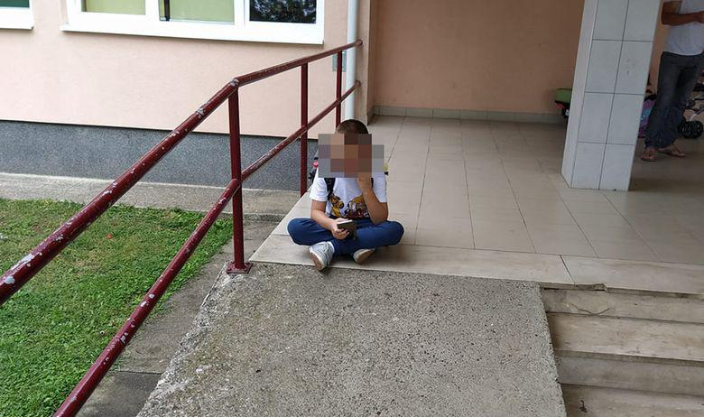 Uplakani prvašić ispred škole