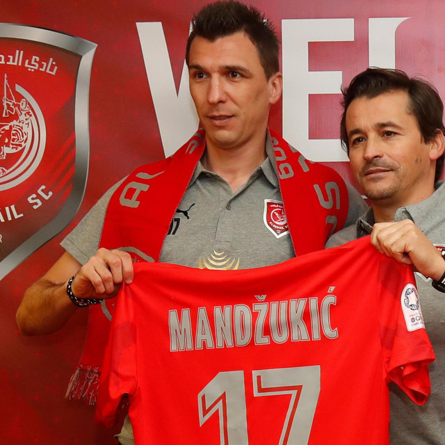 Croatian forward Mario Mandzukic (L) is presented with the number 17 jersey by coach Rui Faria during his introduction as a new player for Qatar's Al Duhail football team on January 2, 2020, in the Qatari capital Doha. - Mandzukic had previously played for Germany's Bayern Munich, Spain's Atletico Madrid and Italy's Juventus before signing for the Qatar club. (Photo by KARIM JAAFAR/AFP)