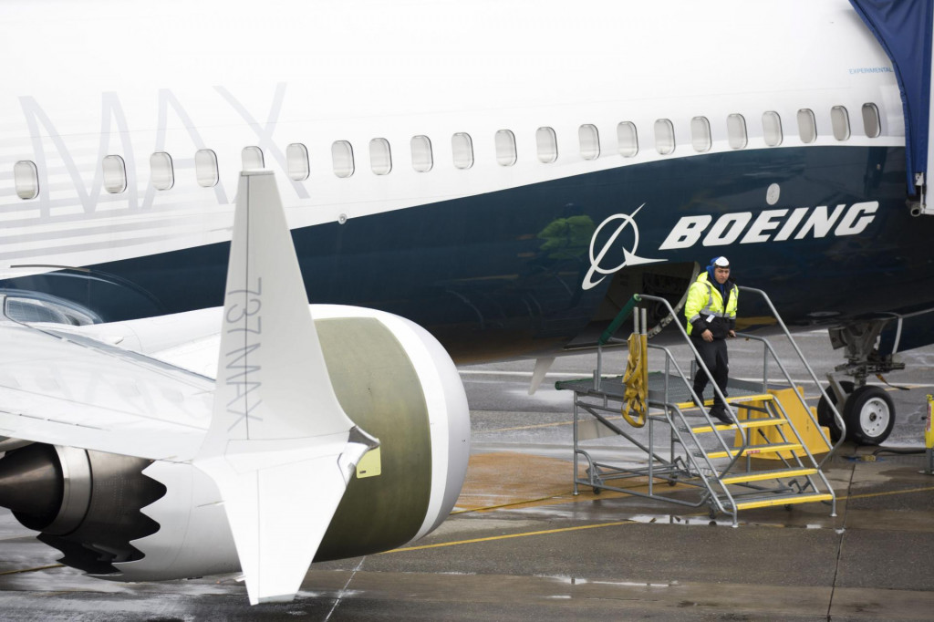 (FILES) In this file photo taken on March 12, 2019 a stands next to a Boeing 737 MAX 9 airplane on the tarmac at the Boeing Renton Factory in Renton, Washington. - Boeing sent internal documents to the US Congress in December, including communications in which employees mocked regulators and brag that they can certify the 737 MAX with minimal pilot training. Among these messages are exchanges between test pilots at Boeing who report problems with flight simulators that replicate actual flight conditions, the aircraft manufacturer explains in a statement released on January 9, 2020. (Photo by Jason Redmond/AFP)