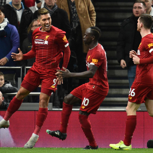 Liverpool's Brazilian midfielder Roberto Firmino (L) celebrates scoring the opening goal during the English Premier League football match between Tottenham Hotspur and Liverpool at Tottenham Hotspur Stadium in London, on January 11, 2020. (Photo by Glyn KIRK/AFP)/RESTRICTED TO EDITORIAL USE. No use with unauthorized audio, video, data, fixture lists, club/league logos or 'live' services. Online in-match use limited to 120 images. An additional 40 images may be used in extra time. No video emulation. Social media in-match use limited to 120 images. An additional 40 images may be used in extra time. No use in betting publications, games or single club/league/player publications./