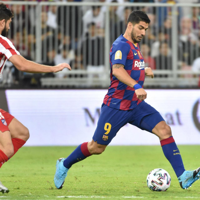 Barcelona's Uruguayan forward Luis Suarez (R) passes the ball during the Spanish Super Cup semi final between Barcelona and Atletico Madrid on January 9, 2020, at the King Abdullah Sport City in the Saudi Arabian port city of Jeddah. - The winner will face Real Madrid in the final on January 12. (Photo by FAYEZ NURELDINE/AFP)