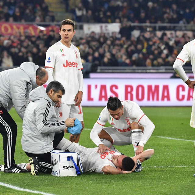 Juventus' Portuguese forward Cristiano Ronaldo (C) tends to Juventus' Turkish defender Merih Demiral after he was injured during the Italian Serie A football match AS Roma vs Juventus on January 12, 2020 at the Olympic stadium in Rome. (Photo by Tiziana FABI/AFP)