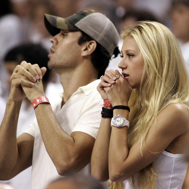 Former tennis player Anna Kournikova (R) of Russia and boyfriend Enrique Iglesias (L) of Spain watches during Game 3 of the NBA finals between the Miami Heat and the Dallas Mavericks at American Airlines Arena in Miami 13 June 2006. The Heat with 42 points in the 98-96 win but still trail the best-of-seven game series 2-1. AFP PHOTO/Jeff HAYNES (Photo by JEFF HAYNES/AFP)