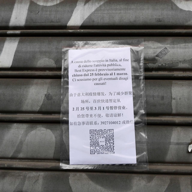 "A picture shows a board reading ""As a consequence of the current health situaion, our stablishment has decided to suspend its activity from February 25 until March 1"", on an iron curtain of a shop in the Chinese district of Milan on February 25, 2020. - The decision to close the stores was made by the Chinese community of the city of Milan as a consequence of the current health situation, following the outbreak of the new coronavirus. Several towns in northern Italy have been put under isolation measures in an attempt to stem the spread of the virus. Seven people in Italy have so far died after catching the virus, all of whom were either elderly or had pre-existing conditions. (Photo by Miguel MEDINA/AFP)"