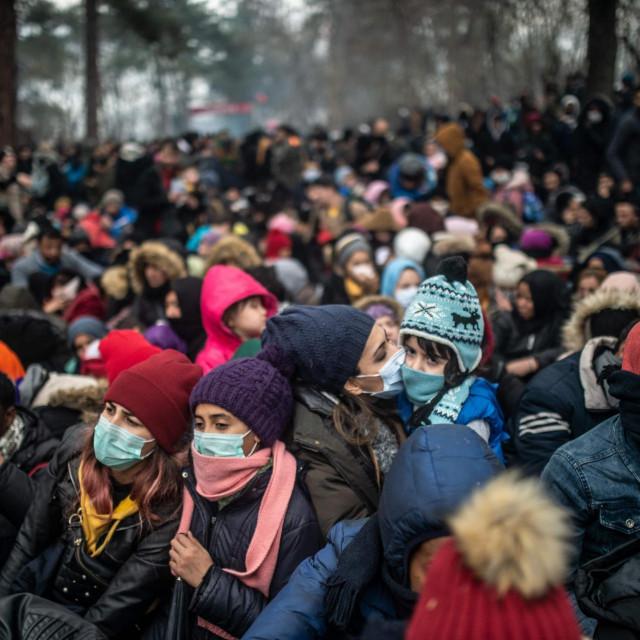 Migranti sa zaštitnim maskama čekaju na tursko-grčkoj granici