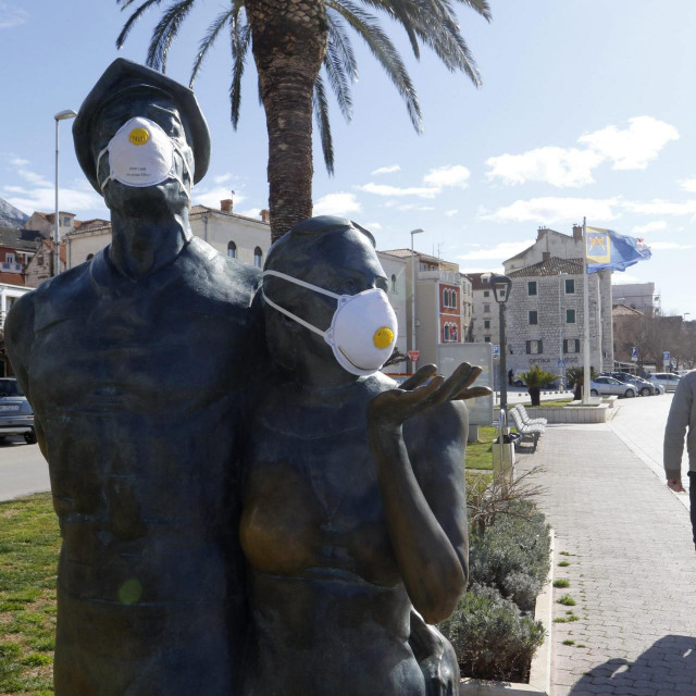 Skulptura U korak s vremenom, poznatija kao Spomenik turizmu opremljena zastitnim maskama
