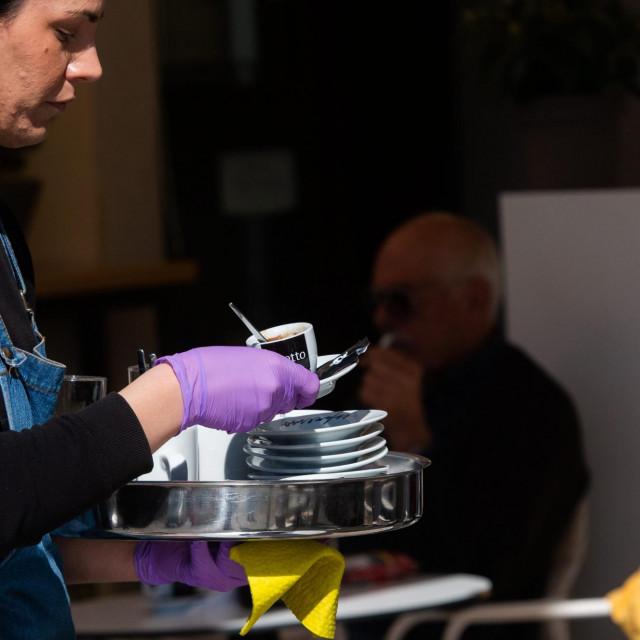 Split, 160320.<br /> Na podrucju Dalmacije jos nije zabiljezen niti jedan slucaj zaraze korona virusom dok je na podrucju RH 56 zarazenih osoba. Zivot se odvija normalno iako se vidi promjena u svakodnevnim navikama gradjana.<br /> Na fotografiji: konobarica sa zastitnim rukavicama na rivi<br />
