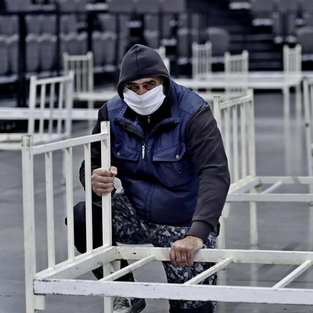 Split, 230320.<br /> Clanovi Hrvatskog Crvenog kriza i pripadnici Hrvatske vojske jutros su poceli postavljati krevete u Spaladium arenu u slucaju povecanja zarazenih koronavirusom.<br /> Za sada u karanteni ima sto kreveta.<br /> Na fotografiji: postavljanje kreveta u dvoranu<br />