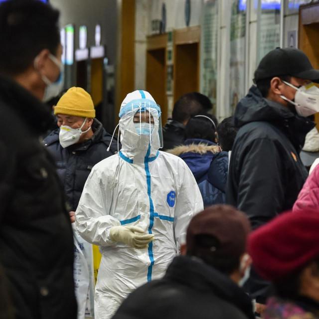 A medical staff member (C) wearing protective clothing to help stop the spread of a deadly virus which began in the city, walks at the Wuhan Red Cross Hospital in Wuhan on January 24, 2020. - Chinese authorities rapidly expanded a mammoth quarantine effort aimed at containing a deadly contagion on January 24 to 13 cities and a staggering 41 million people, as nervous residents were checked for fevers and the death toll climbed to 26. (Photo by Hector RETAMAL/AFP)