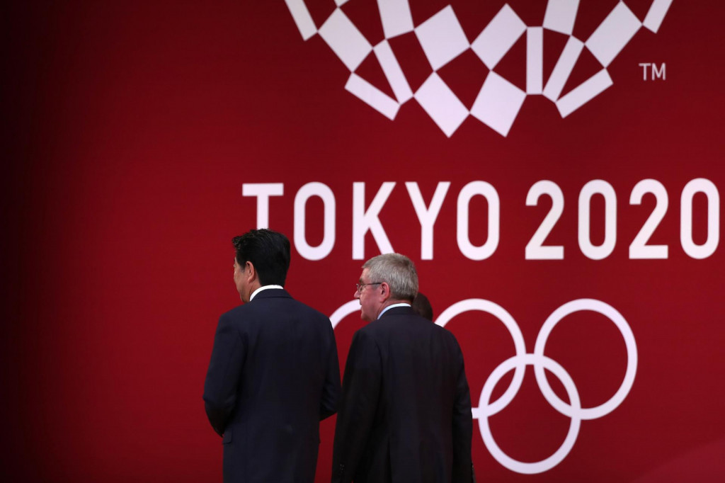 """(FILES) In this file photo taken on July 24, 2019 International Olympic Committee president Thomas Bach (R) walks with Japan's Prime Minister Shinzo Abe (L) as they leave the stage during a ceremony marking one year before the start of the Tokyo 2020 Olympic Games in Tokyo. - apan has asked for a one-year postponement of the Tokyo 2020 Games over the global coronavirus pandemic, and the International Olympic Committee has agreed, the country's prime minister said on March 24, 2020. """"I proposed to postpone for about a year and president Bach responded with 100 percent agreement,"""" Shinzo Abe told reporters referring to Thomas Bach, head of the IOC. (Photo by Behrouz MEHRI/AFP)"""