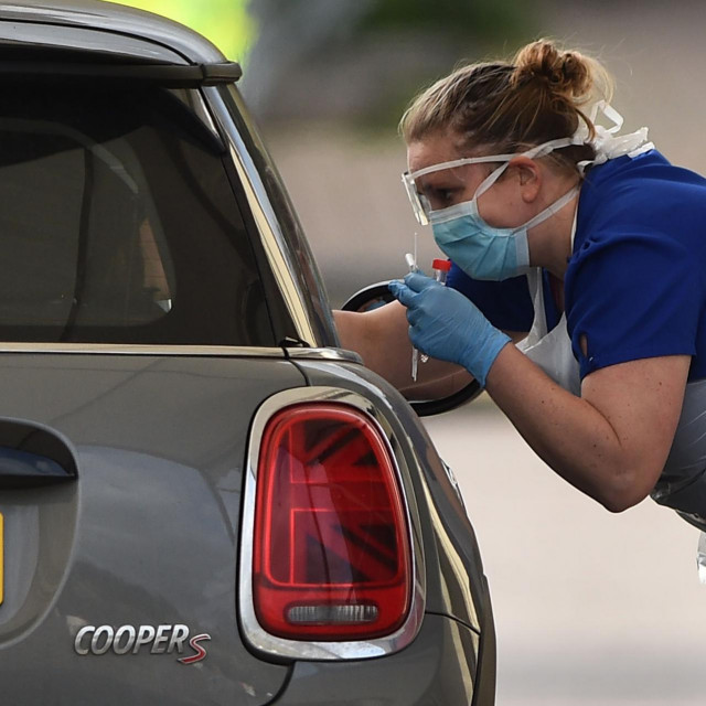 A medical staff member tests an NHS worker for the novel coronavirus COVID-19 at a drive-in facility set up in the carpark of Chessington World of Adventures in Chessington, Greater London on March 28, 2020. - Britain on March 24 said it will open a 4,000-bed field hospital at a London exhibition centre to treat coronavirus cases in the latest measure to tackle the outbreak after the government ordered a nationwide lockdown. (Photo by Glyn KIRK/AFP)