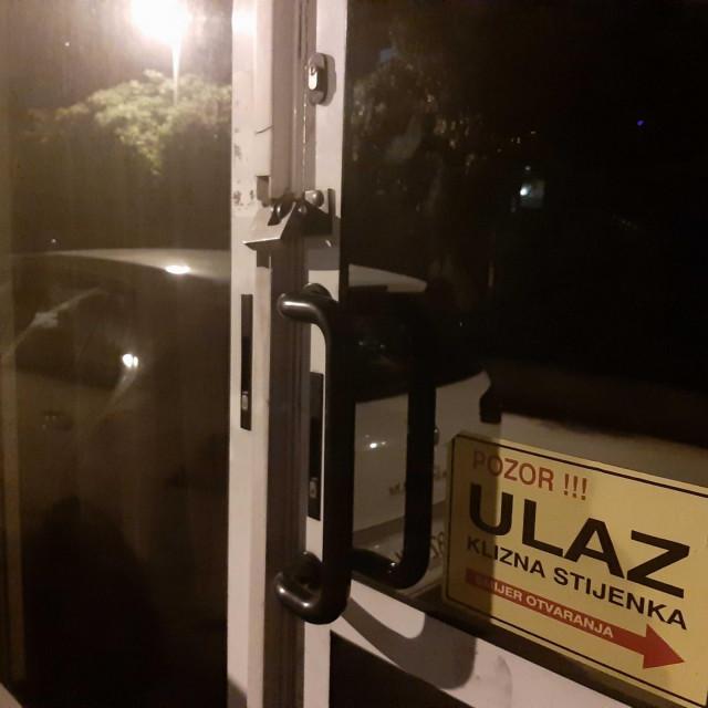 Lokot na ulaznim vratima kafića sa zatamnjenim staklima