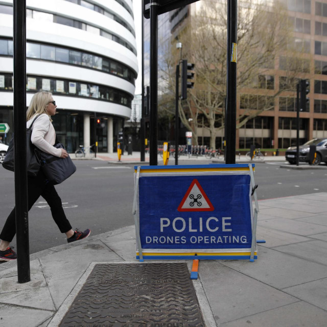 """A picture shows a sign warning of police drones in operation in central London on April 6, 2020, as life in Britain continues during the nationwide lockdown to combat the novel coronavirus pandemic. - British Prime Minister Boris Johnson was in St Thomas' hospital on Monday undergoing tests after suffering """"persistent"""" symptoms of coronavirus for 10 days, but colleagues insisted he remains in charge of the government. (Photo by Tolga AKMEN/AFP)"""