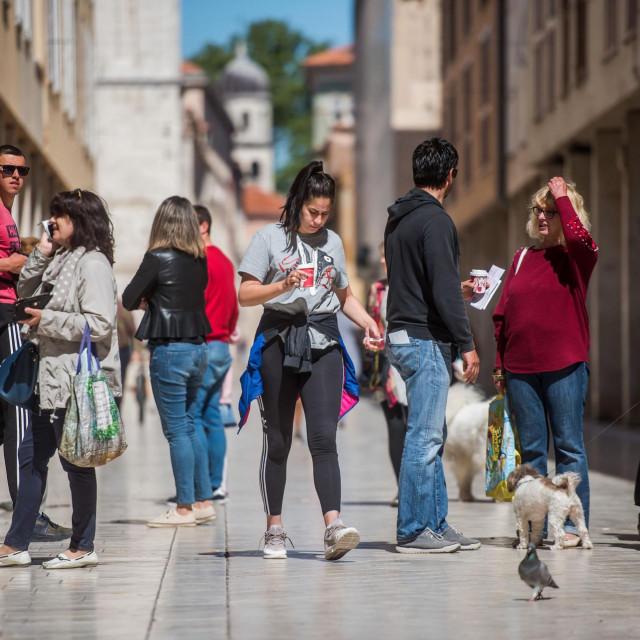 Zadarski Poluotok pun je ljudi, a do skorog otvaranja kafica Zadrani sa kavama za van uzivaju na gradskim trgovima i zelenim povrsinama.