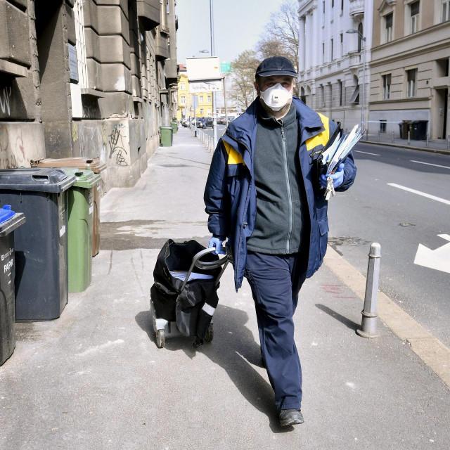 Zagreb, 270320.<br /> Zivot u centru grada peti dan nakon potresa i za vrijeme pandemije koronavirusa.<br /> Na fotografiji: postar raznosi postu u Ulici Eugena Kumicica.<br />