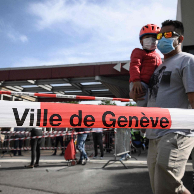 A father and his son wearing protective face masks queue behind warning police tape at a free food distribution on May 9, 2020 in Geneva as the COVID-19 pandemic casts a spotlight on the usually invisible poor people of Geneva, one of the world's most expensive cities. (Photo by Fabrice COFFRINI/AFP)