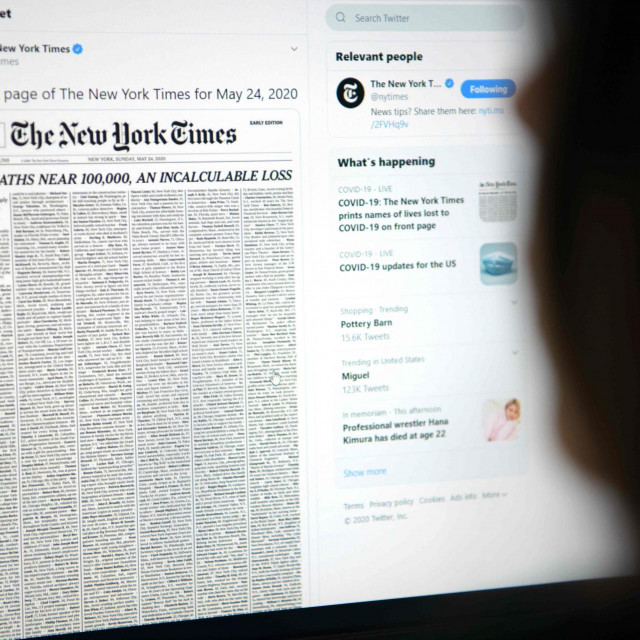 This picture taken on May 23, 2020, in Los Angeles, California, shows a woman looking at a computer screen with a tweet by the New York Times newspaper account showing the early edition front page of May 24, 2020, with a list of 1,000 names printed on it, that represents 1% of the lives lost due to the novel coronavirus pandemic, COVID-19, in the US. (Photo by Agustin PAULLIER/AFP)