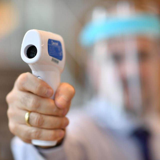 A member of staff wearing a face shield uses a laser thermometer to test customer's temperatures in a Furniture Village store in Croydon, in south-east London on June 5, 2020, following the easing of the lockdown restrictions during the novel coronavirus COVID-19 pandemic. - UK retail sales dived by a record 18.1 percent in April with the country in coronavirus lockdown. Most shops will soon be allowed to reopen, as Britain -- with the world's second-highest death toll in the coronavirus outbreak -- took its biggest step out of lockdown this week. (Photo by BEN STANSALL/AFP)