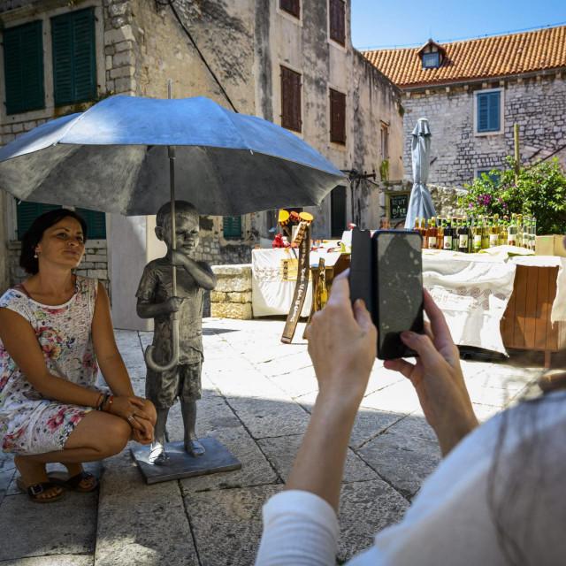 Sibenik, 030720.<br /> Kip Djecak sa kisobranom, rad kipara Kazimira Hraste na trgu ispred svete Barbare<br />