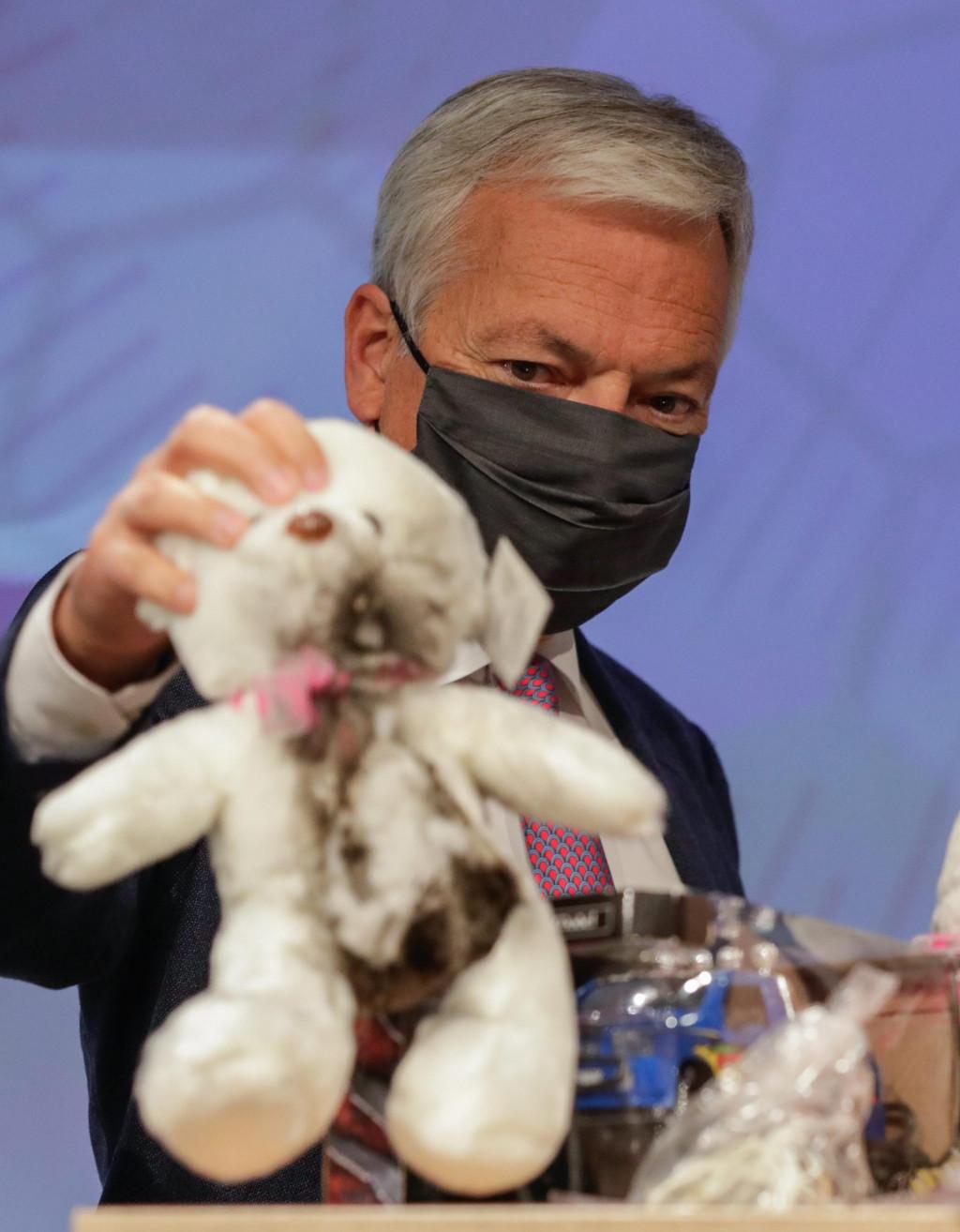 Didier Reynders iz Europske komisije pokazuje na konferenciji u Bruxellesu opasne proizvode među igračkama