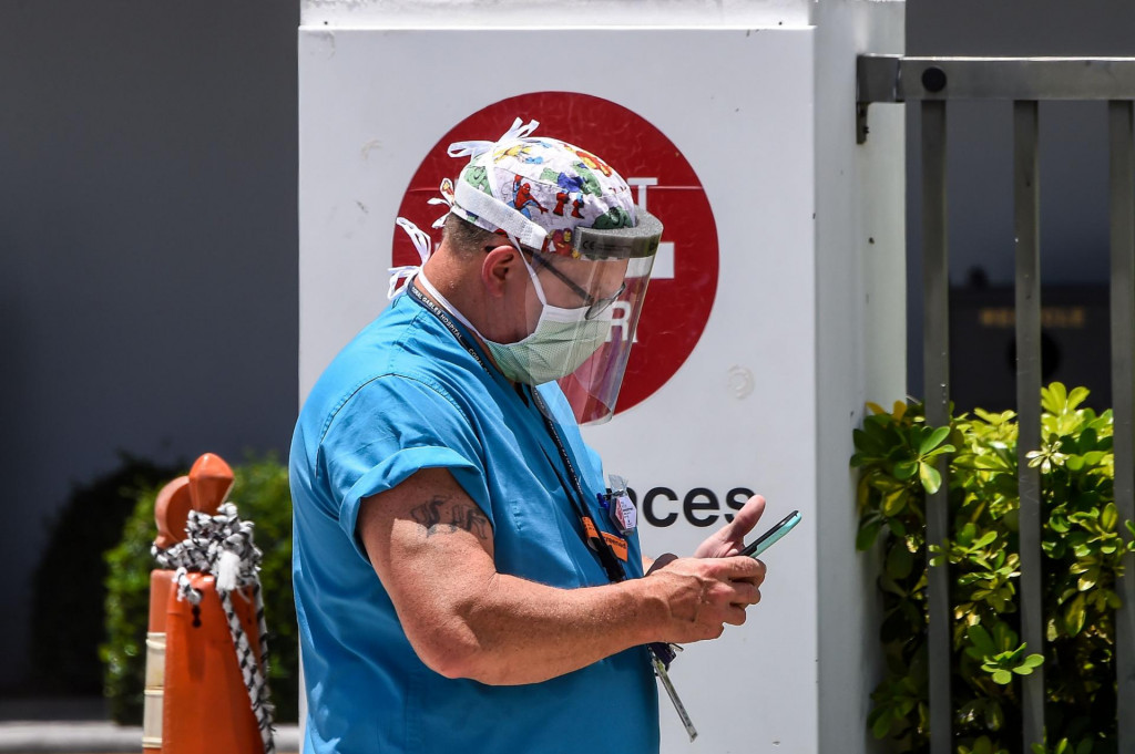 A medic looks at his phone as he walks outside of Emergency at Coral Gables Hospital where Coronavirus patients are treated in Coral Gables near Miami, on July 30, 2020. - Florida has emerged as a major new epicenter of the US battle against the disease, with confirmed cases recently surpassing New York and now second only to California. The state toll has leapt over the past week and more than 6,500 people have died from the disease there, according to health officials. More than 460,000 people have been infected with the virus in Florida, which has a population of 21 million, and a quarter of the state's cases are in Miami. The US has tallied a total of 151,826 deaths from COVID-19, making it the hardest-hit country in the world. (Photo by CHANDAN KHANNA/AFP)