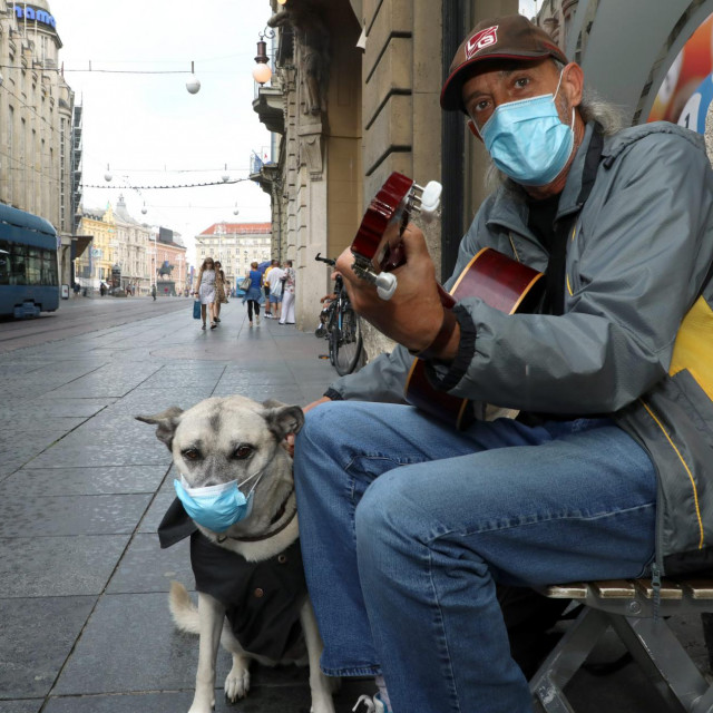 Zagreb, 030820.<br /> Ilica.<br /> Ulicni svirac Roberto i njegov pas Rea sa zastitnim maskama zabavljaju prolaznike.<br />