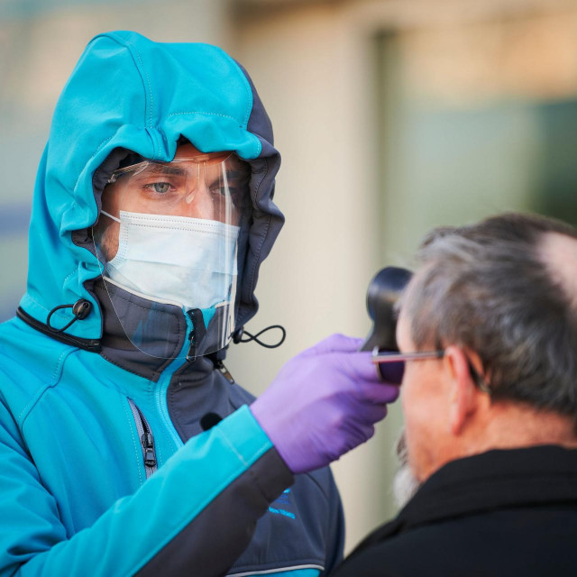 TOPSHOT - A medical worker measures body temperature at one of the entrances of the Community Health Centre in Kranj, Slovenia on March 23, 2020 amid concerns over the spread of the COVID-19 coronavirus. (Photo by Jure Makovec/AFP)