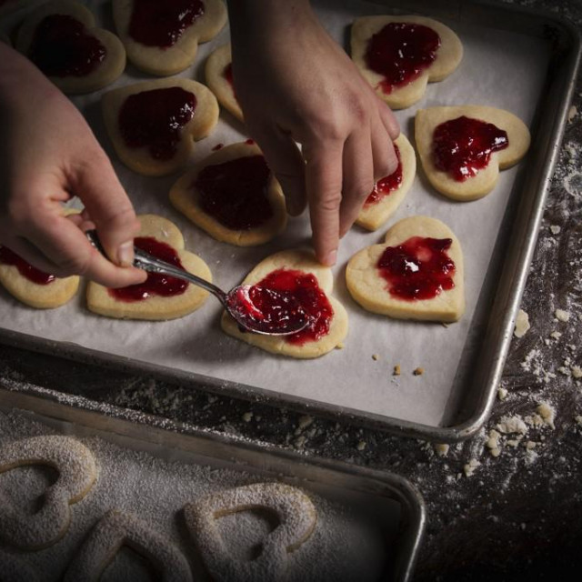 [Utah, USA] Valentine's Day baking, woman spreading raspberry jam on heart shaped biscuits.