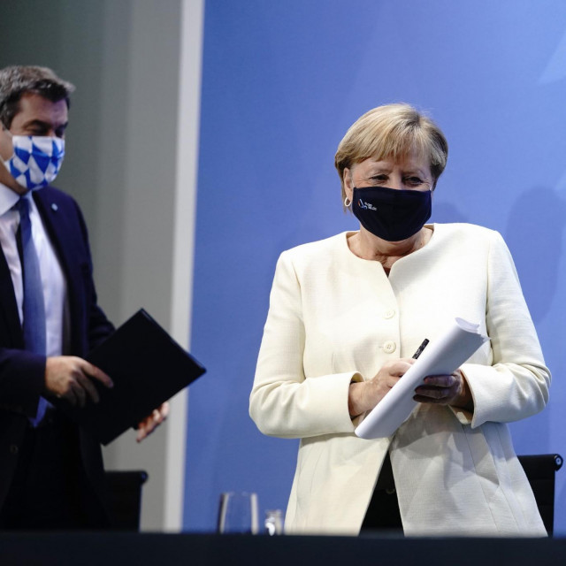 Bavaria's State Premier Markus Soeder and German Chancellor Angela Merkel leave after a press conference after a video conference with State Premiers on the country's response to the new coronavirus pandemic on September 29, 2020 in Berlin. (Photo by Kay Nietfeld/POOL/AFP)