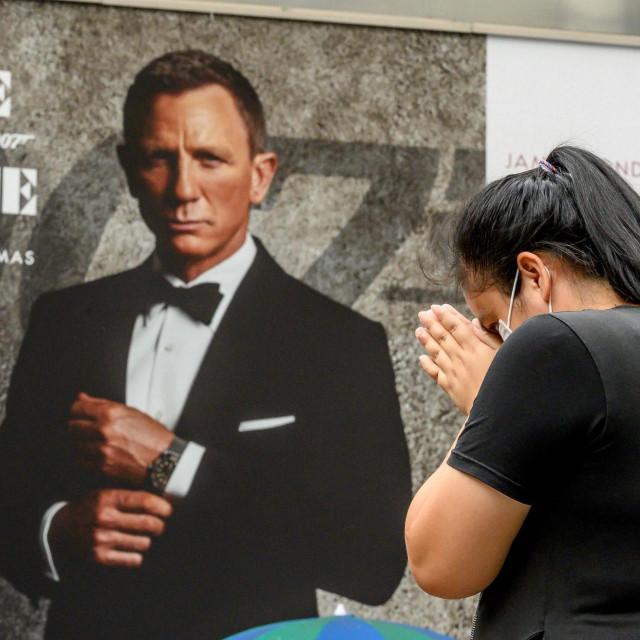 (Simbolična) molitva za kina ispred plakata Bond-filma 'Za smrt nema vremena' pored hrama Erawan u Bangkoku