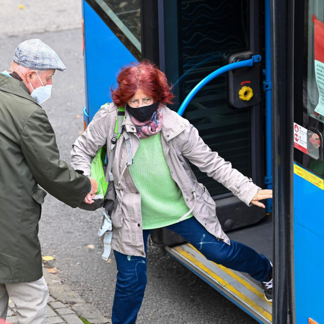Wearing their facemasks, an elderly Hungarian couple get off the bus at the St Janos Hospital of Budapest, 12th district on October 18, 2020, amid the novel coronavirus COVID-19 pandemic. - The new coronavirus COVID-19 was detected by 1474 Hungarian citizens on October 17, 2020, thus increasing the number of infected people identified in Hungary to 46,290. (Photo by ATTILA KISBENEDEK/AFP)