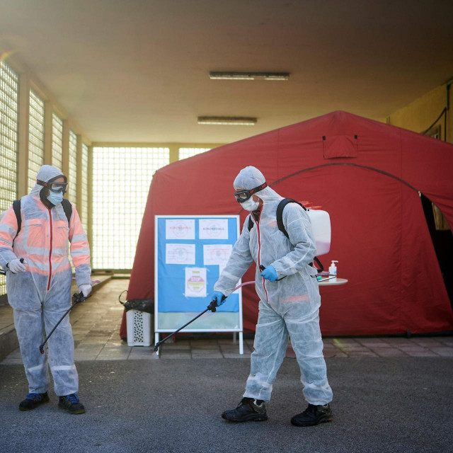 Workers wearing protective clothes disinfect one of the entrances at the Community Health Centre in Kranj, Slovenia, on March 23, 2020 amid concerns over the spread of the COVID-19 coronavirus. (Photo by Jure Makovec/AFP)