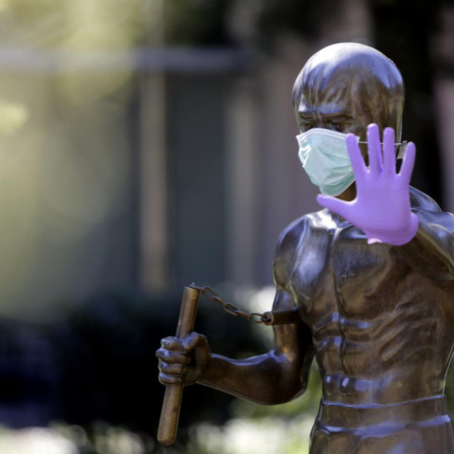 A picture taken on April 2, 2020 shows the statue dedicated to martial arts icon and actor Bruce Lee, wearing surgical gloves and a face mask, in the central park of Mostar as Bosnia Herzegovina records 518 people infected by the COVID-19, the novel coronavirus. - The statue was made by Croatian sculptor Ivan Fijolic and was erected in Mostar's central park, on 2005. (Photo by STR/AFP)/RESTRICTED TO EDITORIAL USE - MANDATORY MENTION OF THE ARTIST UPON PUBLICATION - TO ILLUSTRATE THE EVENT AS SPECIFIED IN THE CAPTION