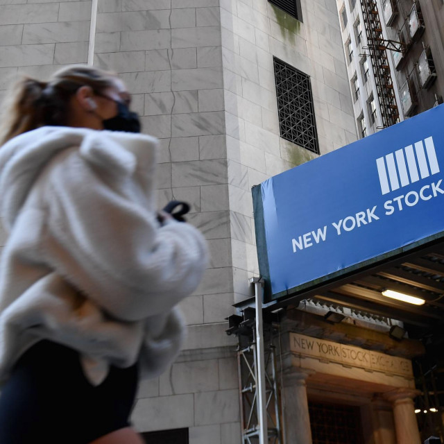 A woman walks past the New York Stock Exchange (NYSE) at Wall Street on November 16, 2020 in New York City. - Wall Street stocks rose early following upbeat news on a coronavirus vaccine and merger announcements in the banking and retail industries. (Photo by Angela Weiss/AFP)