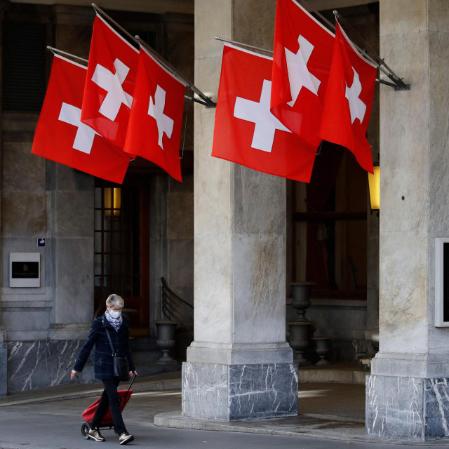 A woman passing by Swiss flags wears a protective face mask in the street ahead of the announcement by Swiss government of new restrictions to fight the Covid-19 outbreak in Bern, on October 27, 2020. - Cases, hospitalisations and deaths in Switzerland have doubled from one week to the next throughout October. (Photo by STEFAN WERMUTH/AFP)