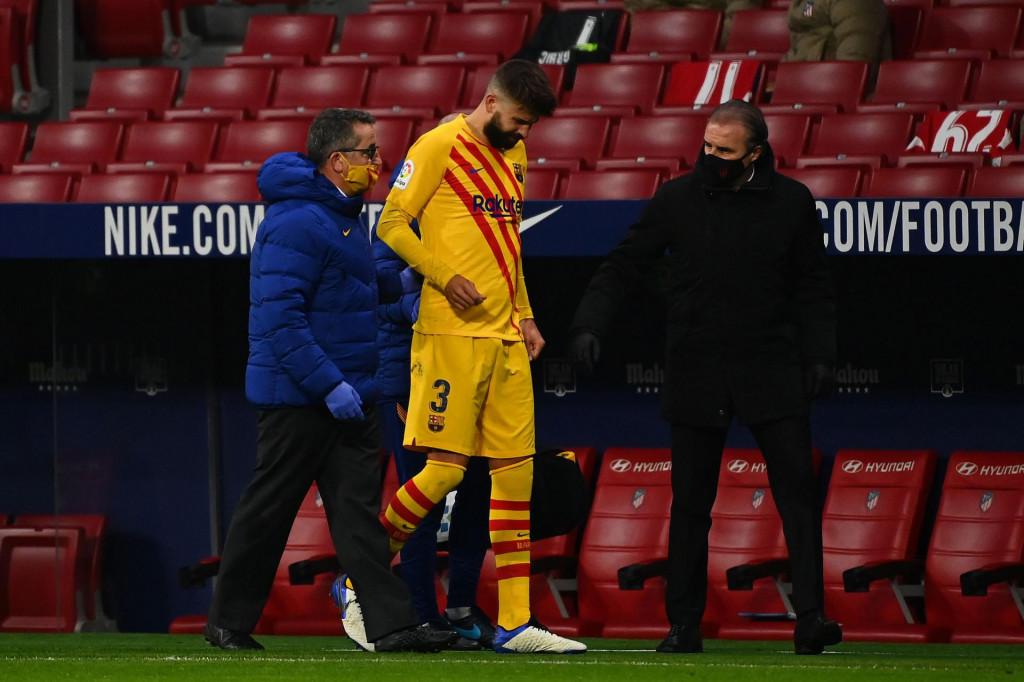 Barcelona's Spanish defender Gerard Pique (C) walks off the pitch after getting injured during the Spanish League football match between Club Atletico de Madrid and FC Barcelona at the Wanda Metropolitano stadium in Madrid on November 21, 2020. (Photo by GABRIEL BOUYS/AFP)
