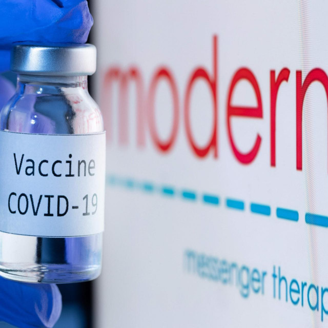 """(FILES) In this file photo taken on November 18, 2020 shows a bottle reading """"Vaccine Covid-19"""" next to the Moderna biotech company logo. - US firm Moderna said it would file requests for emergency authorization of its Covid-19 vaccine in the United States and Europe on November 30, 2020, after full results confirmed a high efficacy estimated at 94.1 percent. """"We believe that our vaccine will provide a new and powerful tool that may change the course of this pandemic and help prevent severe disease, hospitalizations and death,"""" said the company's CEO Stephane Bancel. (Photo by JOEL SAGET/AFP)/-- IMAGE RESTRICTED TO EDITORIAL USE - STRICTLY NO COMMERCIAL USE --"""