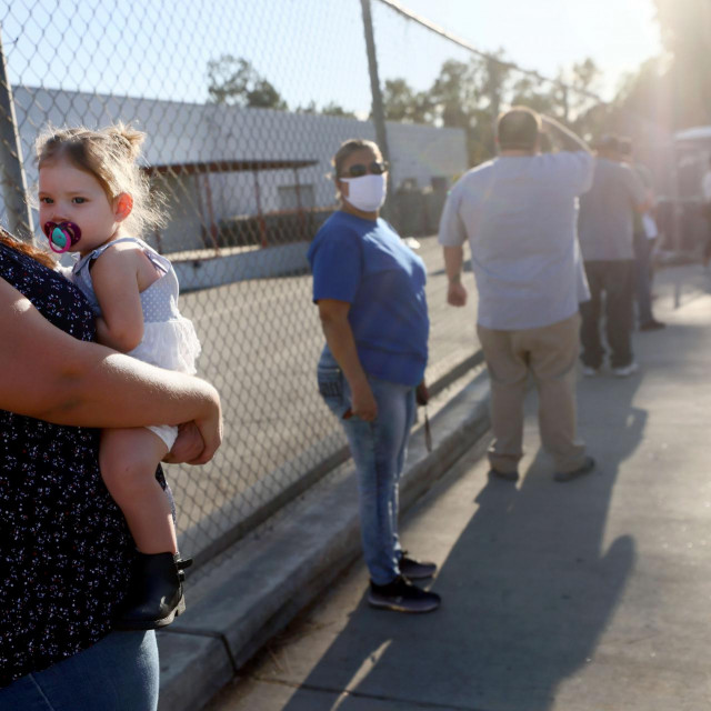 SAN FERNANDO, CALIFORNIA - DECEMBER 2: A woman holds her niece while waiting in line at a walk-up Covid-19 testing site on December 2, 2020 in San Fernando, California. California reported 20,759 new coronavirus cases today, a one-day record for the state, amid a new limited stay-at-home order in Los Angeles County. Mario Tama/Getty Images/AFP<br /> == FOR NEWSPAPERS, INTERNET, TELCOS & TELEVISION USE ONLY ==