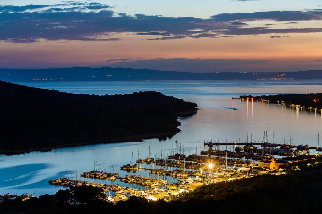 Pogled na grad Cres i ulaz u luku, a u pozadini se vidi Istra