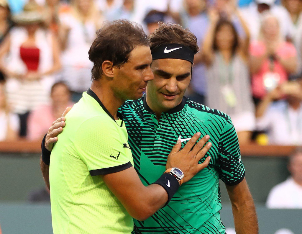 """(FILES) In this file photo Roger Federer of Switzerland shakes hands at the net after his straight sets victory against Rafael Nadal of Spain in their fourth round match during day ten of the BNP Paribas Open at Indian Wells Tennis Garden on March 15, 2017 in Indian Wells, California. - The head of the WTA Tour has voiced support for a merger with the ATP Tour following calls led by Roger Federer and Rafael Nadal to integrate the men's and women's circuits.<br /> In an interview with the New York Times published on May 5, 2020, WTA chief executive Steve Simon said a unified circuit made sense.""""I'm not afraid of the full merger; I never have been,"""" Simon told the Times. (Photo by CLIVE BRUNSKILL/GETTY IMAGES NORTH AMERICA/AFP)"""