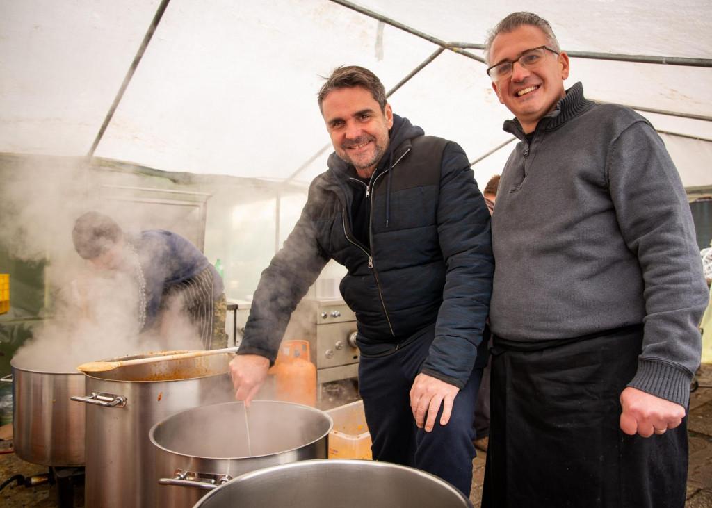 Đani Stipaničev miješa gulaš u društvu Saše Računice, voditelja kuharske ekipe iz Dubrovnika.