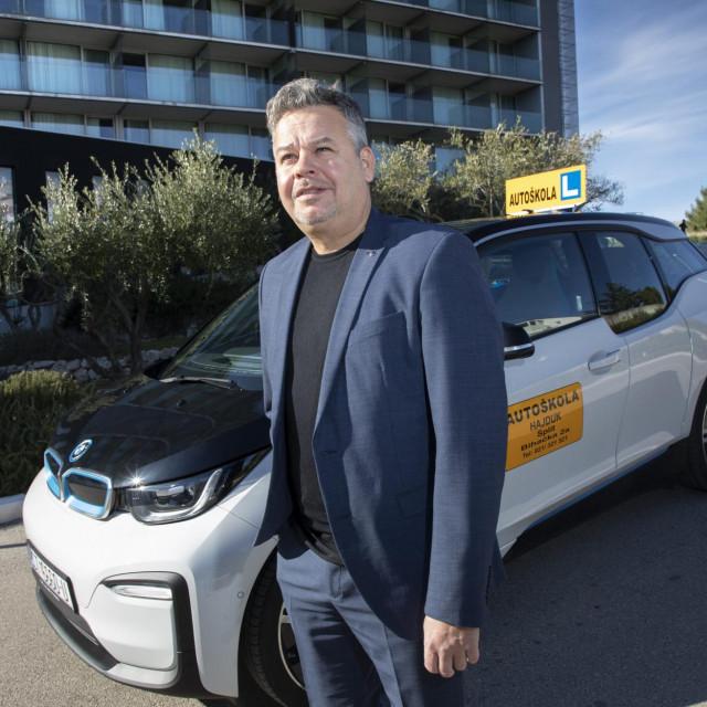 Denis Ožegović, vlasnik autoškole Hajduk pored automobila BMW i3 na električni pogon prilagođenim za poalaganje vozačkog ispita osoba s invaliditetom