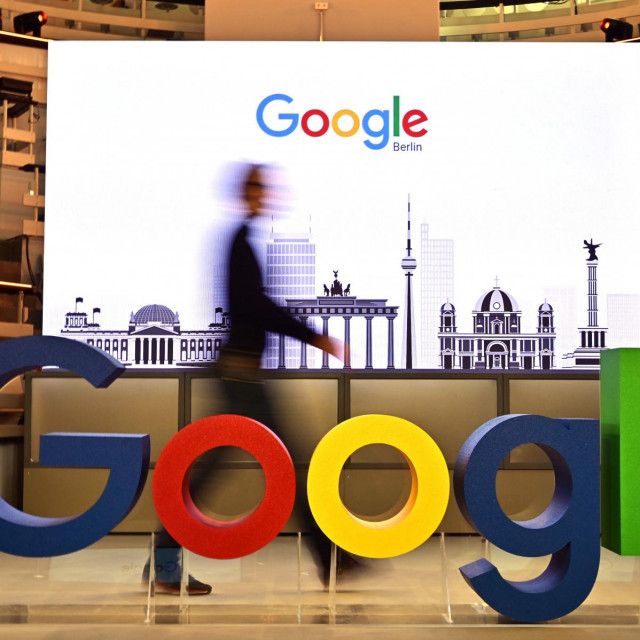 "(FILES) In this file photo taken on January 22, 2019 a technician passes by a logo of US internet search giant Google during the opening day of a new Berlin office of Google in Berlin. - Google will pay partnered media publishers in three countries and offer some users free access to paywalled news sites, the tech giant said June 25, 2020. The announcement comes after legal battles in France and Australia over Google's refusal to pay news organizations for content.In a blog post the firm said they would launch ""a licensing program to pay publishers for high-quality content for a new news experience"" due to launch later this year. (Photo by Tobias SCHWARZ/AFP)"