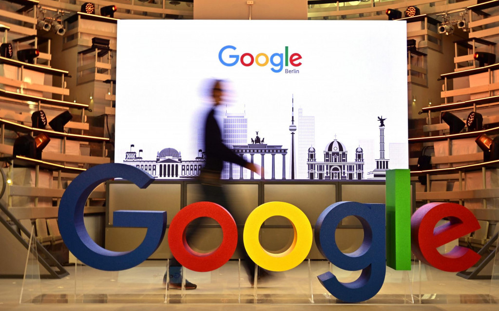 """(FILES) In this file photo taken on January 22, 2019 a technician passes by a logo of US internet search giant Google during the opening day of a new Berlin office of Google in Berlin. - Google will pay partnered media publishers in three countries and offer some users free access to paywalled news sites, the tech giant said June 25, 2020. The announcement comes after legal battles in France and Australia over Google's refusal to pay news organizations for content.In a blog post the firm said they would launch """"a licensing program to pay publishers for high-quality content for a new news experience"""" due to launch later this year. (Photo by Tobias SCHWARZ/AFP)"""