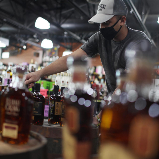 MIAMI, FLORIDA - FEBRUARY 03: Javier Ruis stocks liquor at Jensen's Liquors on February 03, 2021 in Miami, Florida. The Distilled Spirits Council reported that U.S. distillers� revenue grew 7.7% to $31.2 billion last year, marking the fastest growth and highest sales for at least 40 years. Alcohol that sold for above $40 per 750 milliliters accounted for 40% of the U.S. spirits industry�s growth in 2020, compared with 34% in 2019. Joe Raedle/Getty Images/AFP<br /> == FOR NEWSPAPERS, INTERNET, TELCOS & TELEVISION USE ONLY ==