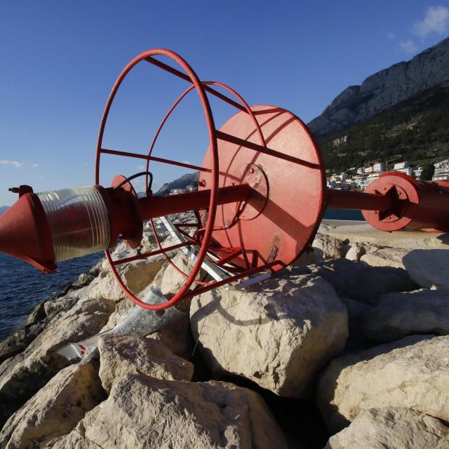 Baska Voda, 140221.<br /> Lanterna, svjetionik, na lukobranu lucice u mjestu Baska Voda kod Makarske, koju je oborila olujna Bura koja na makarskom podrucju puse sa udarima do 110 km/h.<br /> Na fotografiji: Oborena lanterna na ulazu u baskovodsku lucicu.<br />