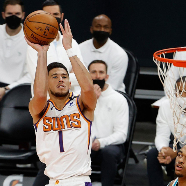 PHOENIX, ARIZONA - FEBRUARY 24: Devin Booker #1 of the Phoenix Suns attempts a shot over Cody Zeller #40 of the Charlotte Hornets during the second half of the NBA game at Phoenix Suns Arena on February 24, 2021 in Phoenix, Arizona. NOTE TO USER: User expressly acknowledges and agrees that, by downloading and or using this photograph, User is consenting to the terms and conditions of the Getty Images License Agreement. Christian Petersen/Getty Images/AFP<br /> == FOR NEWSPAPERS, INTERNET, TELCOS & TELEVISION USE ONLY ==