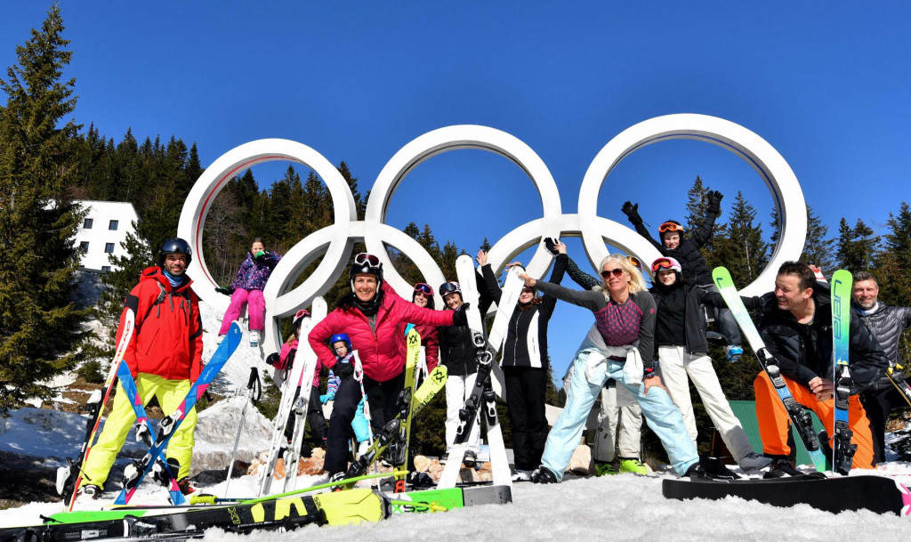 Skiers pose in front of the Olympic Rings on the slopes of Mount Jahorina near the Bosnian capital of Sarajevo, on February 26, 2021. - Although some disease prevention measures have implemented, most transport systems are functional and many accommodation option are available. Jahorina Olympic centre is recording a high numbers of visitors in the winter 2020/21 season. Domestic visitors as well as from neighbouring countries, where ski centres have been closed for most of the season in order to prevent spread of the new coronavirus(Covid-19). (Photo by ELVIS BARUKCIC/AFP)