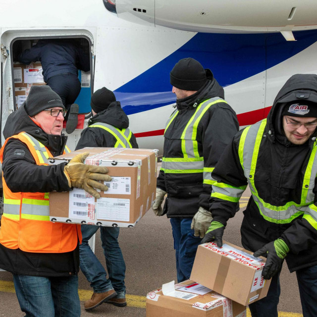 Workers unload boxes of Moderna Covid-19 vaccines from a Falcon aircraft, in Saint-Pierre, in the French northern Atlantic archipelago of Saint-Pierre-et-Miquelon, on March 20, 2021. - French Seas Minister arrived to Saint-Pierre and Miquelon to deliver 9,600 doses of Moderna Covid-19 vaccines with a Falcon military flight, ahead of a Covid-19 vaccination campaign in the territory. (Photo by Chantal Briand/AFP)