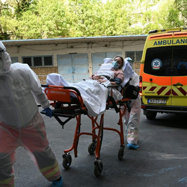 Participants of an exercise wear protective suits as they transport a presumed patient to the Kutvolgyi hospital in Budapest, Hungary, on August 27, 2020, during a training for medical staff, police and military officials, where the arrival of a tourist bus with coronavirus-infected travellers was simulated. (Photo by ATTILA KISBENEDEK/AFP)